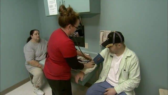 Man having blood pressure taken while woman looks on
