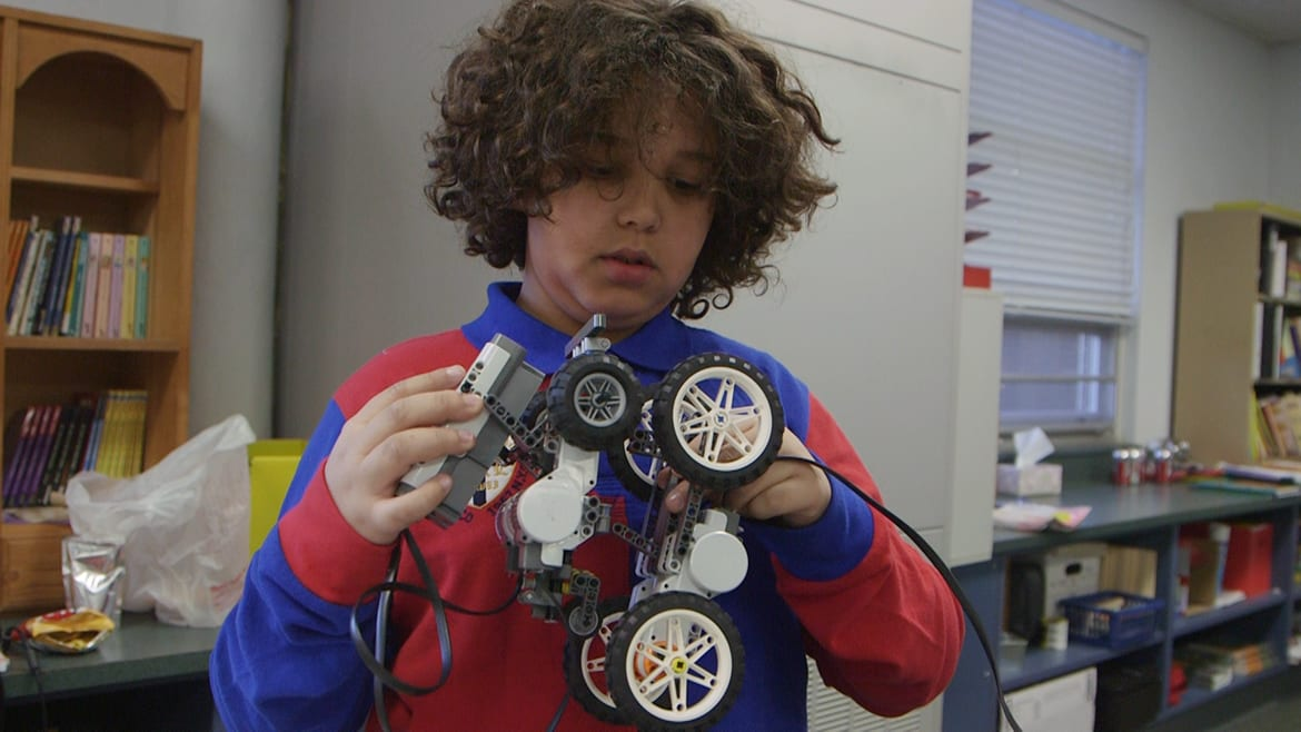 Young boy holding up electrical device with wheels.
