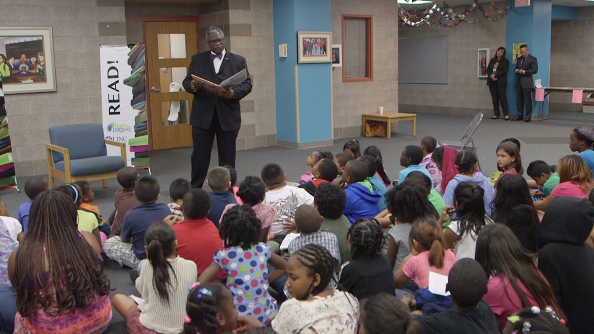 Kansas City, Missouri Mayor Sly James stands and reads in front of group of students sitting on the floor.