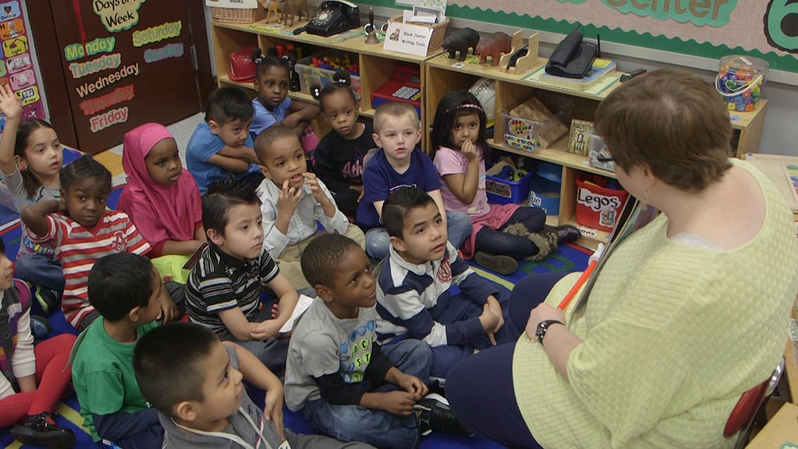 Picture of children sitting on the floor listening to teacher read book.