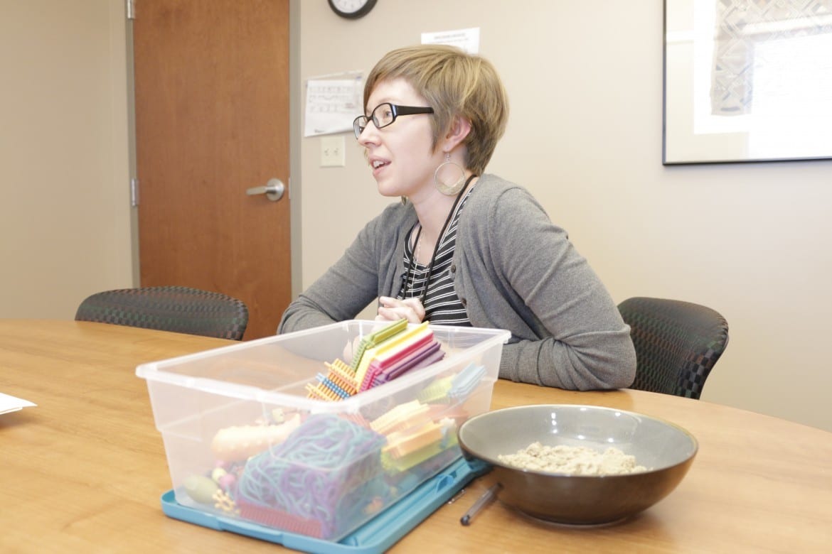 A woman sits at a conference table next to small building blocks and a bowl of sensory sand.