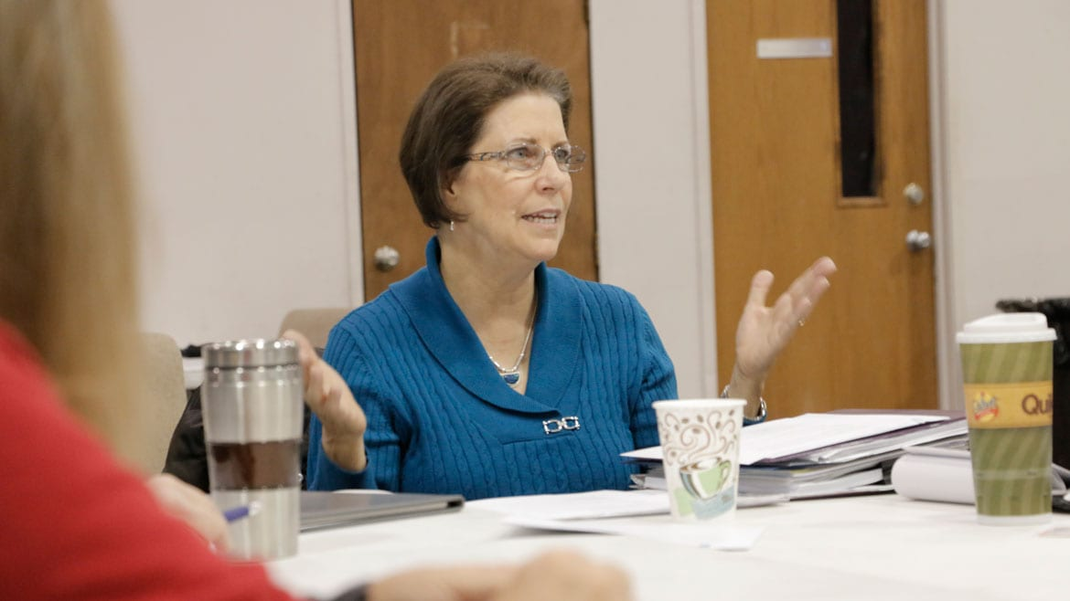 a woman in a blue sweater gestures with her hands as she speaks in a meeting