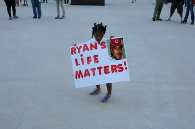 Neriha Stokes, the daughter of Ryan Stokes holding sign at vigil that says Ryan's Life Matters