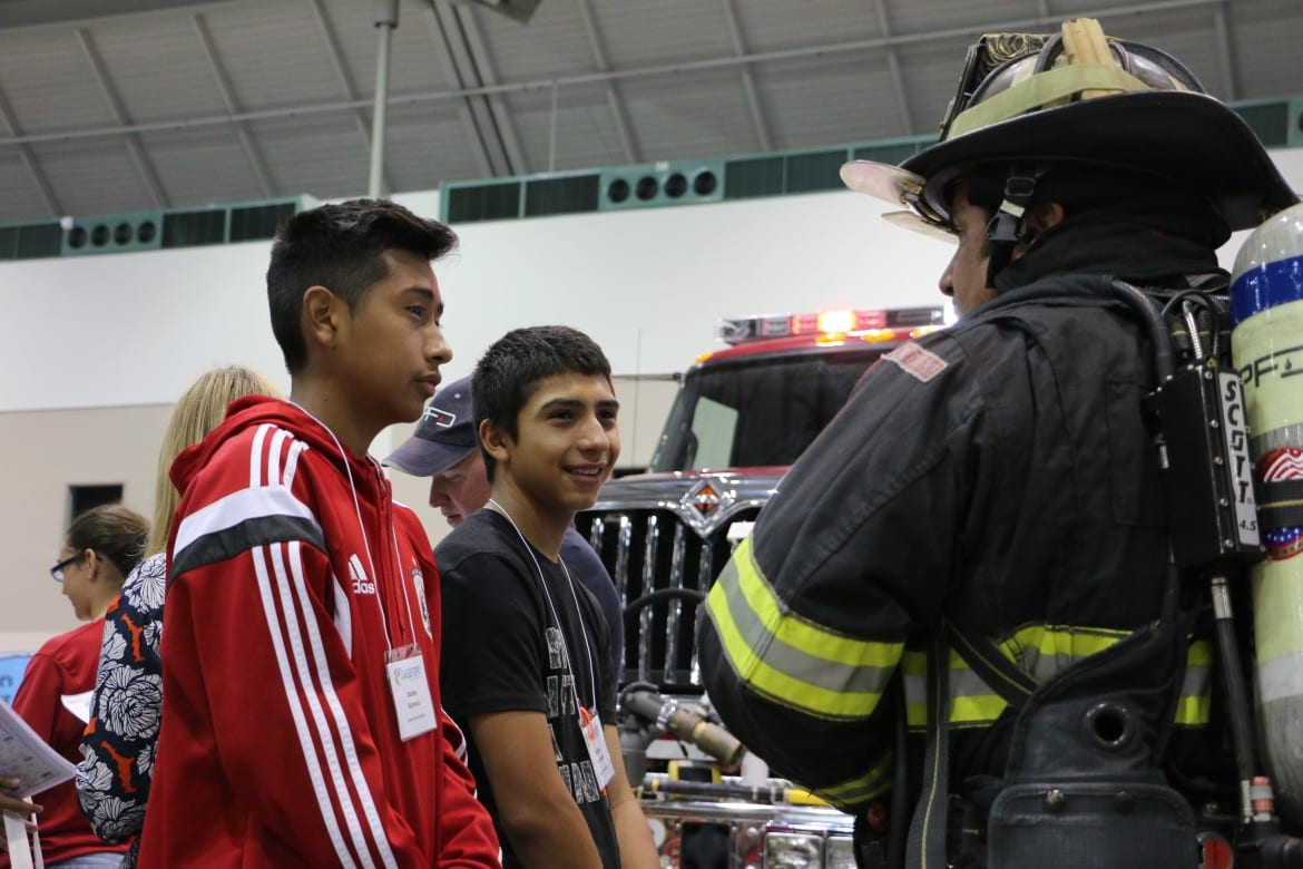Jesus Isidor, 14, left, and Samuel Ortiz, 15, a freshman and sophomore, respectively, at Olathe North High School, got some information from Overland Park firefighter Brian Minick, who piqued their interest by telling them the department pays bonuses for personnel who are fluent in Spanish.