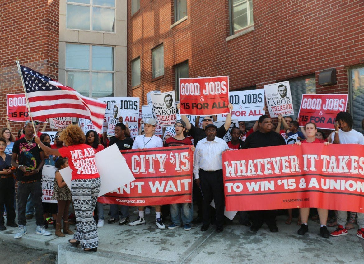 Protestors stand outside building