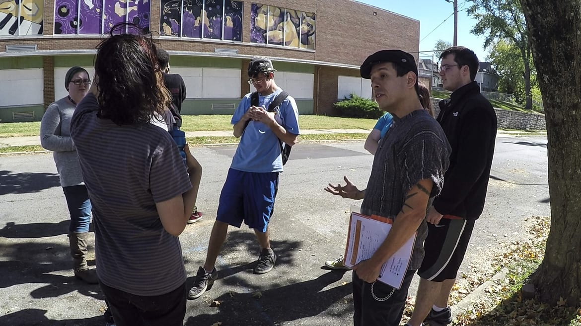 Kansas City Art Institute instructor Hector Casanova, right, talks with his illustration students as they see their murals in place on the elementary school building.