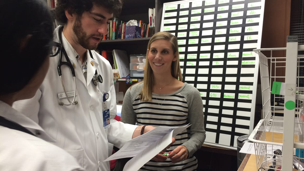 KU Med student Maddy Breedan (right) talks about patient treatment with fellow student Adam Stizmann at the JayDoc Free Clinic. Med students must weigh income, patient needs when choosing a future path. (Photo: Alex Smith | Heartland Health Monitor)
