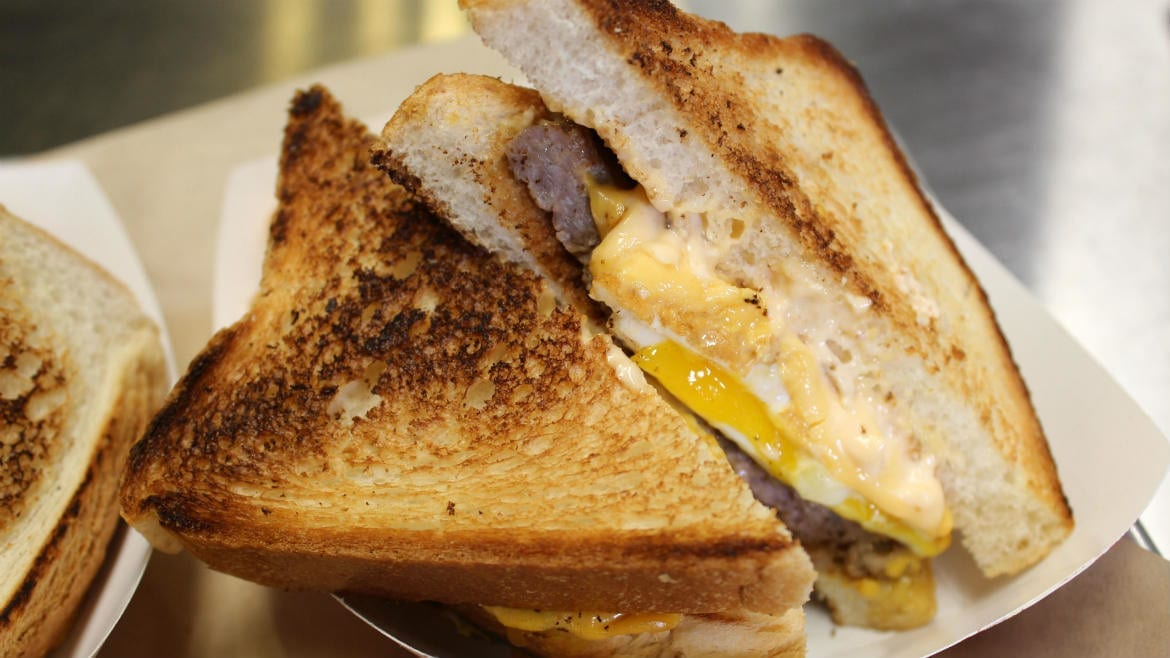 Photo of toasted sandwich with egg, cheese and sausage.