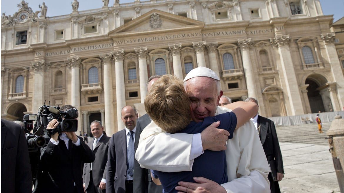 The pope gives a young boy a hug at the vatican