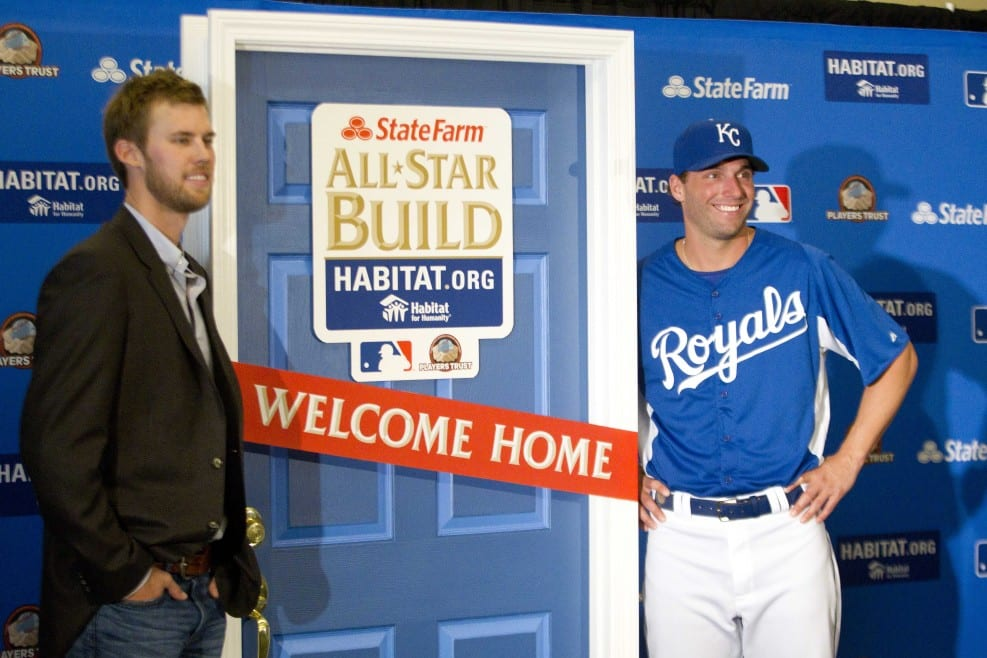 Two baseball players standing near a Habitat for Humanity door
