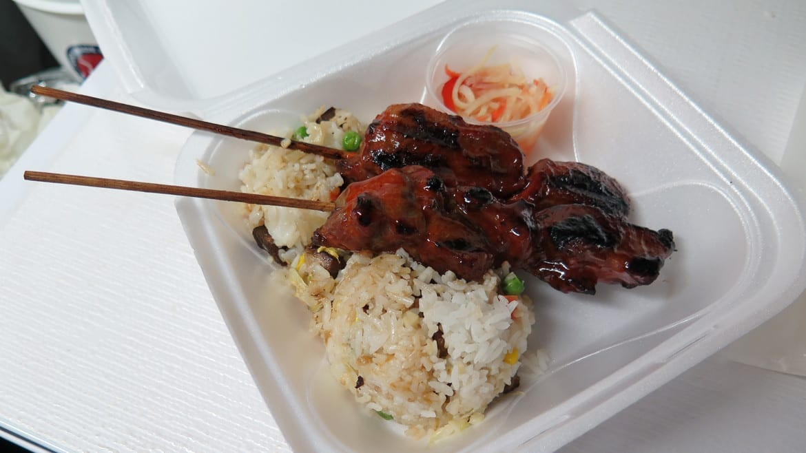 A pair of pork skewers over rice.