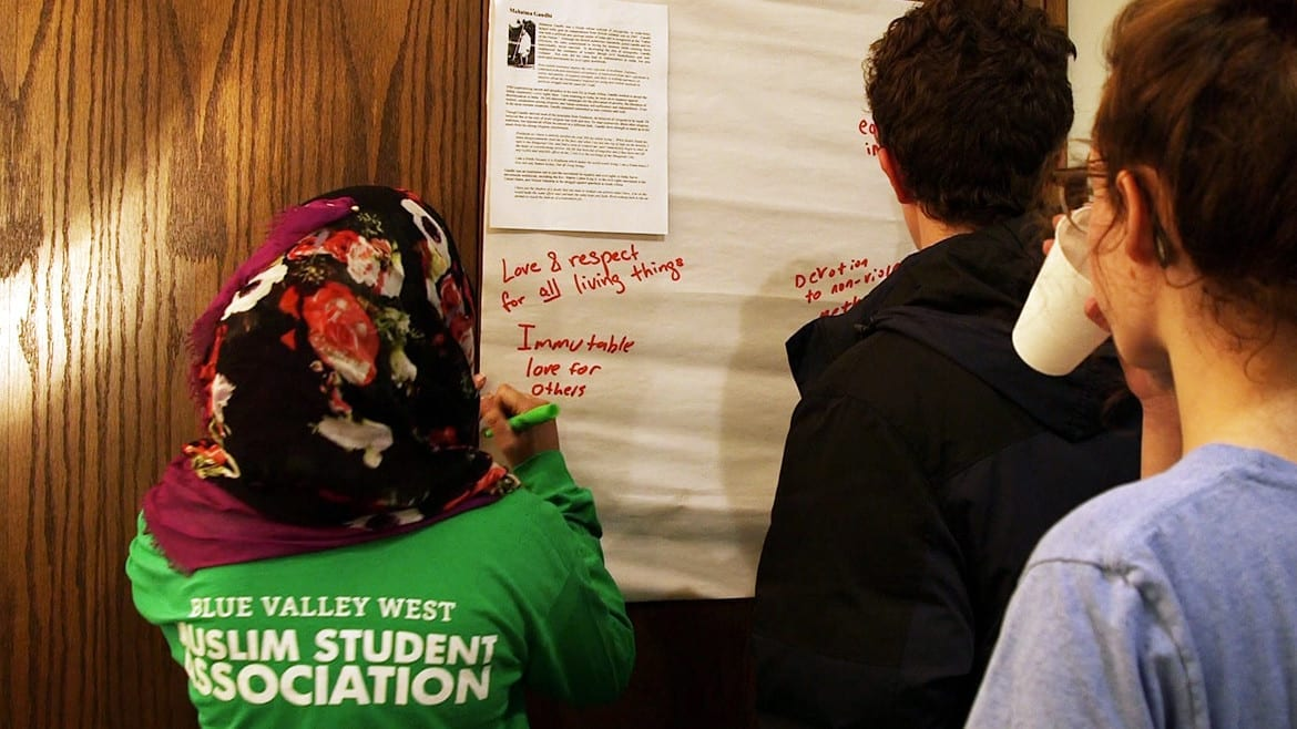 Young woman in green shirt writes on paper.