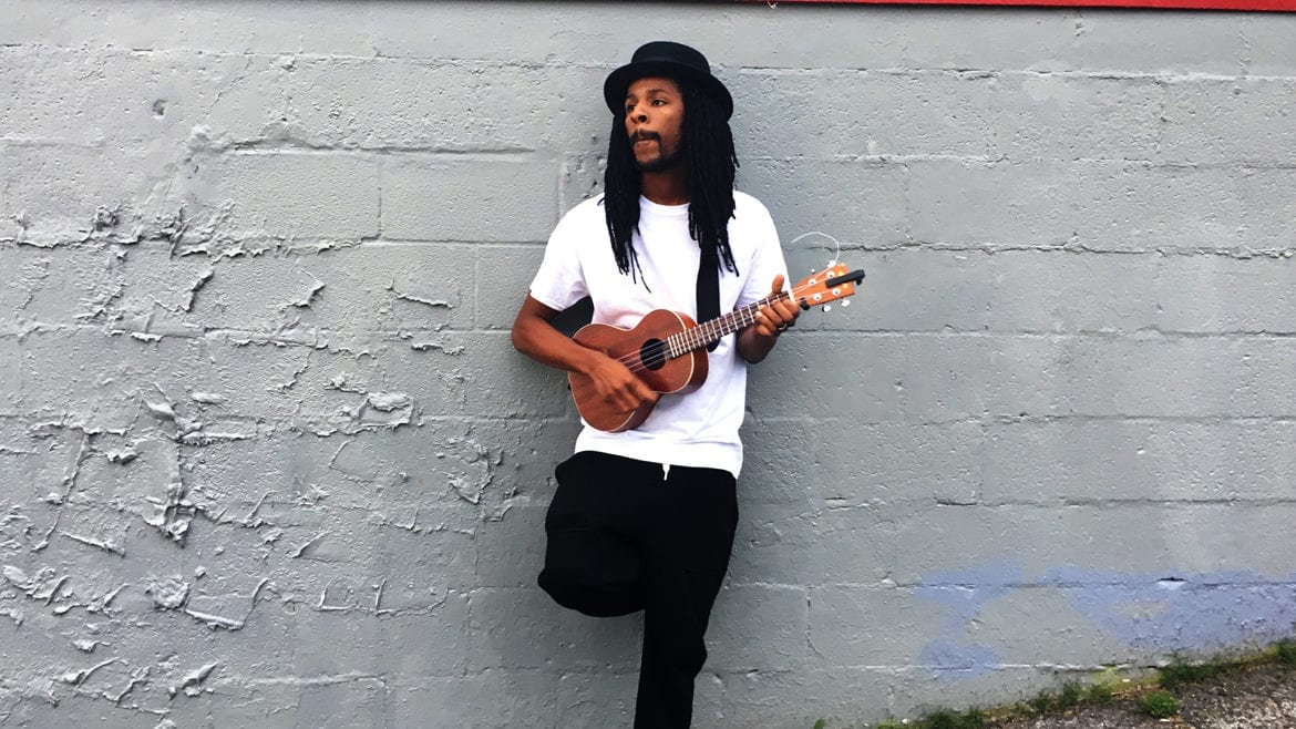 Man standing against wall with ukulele