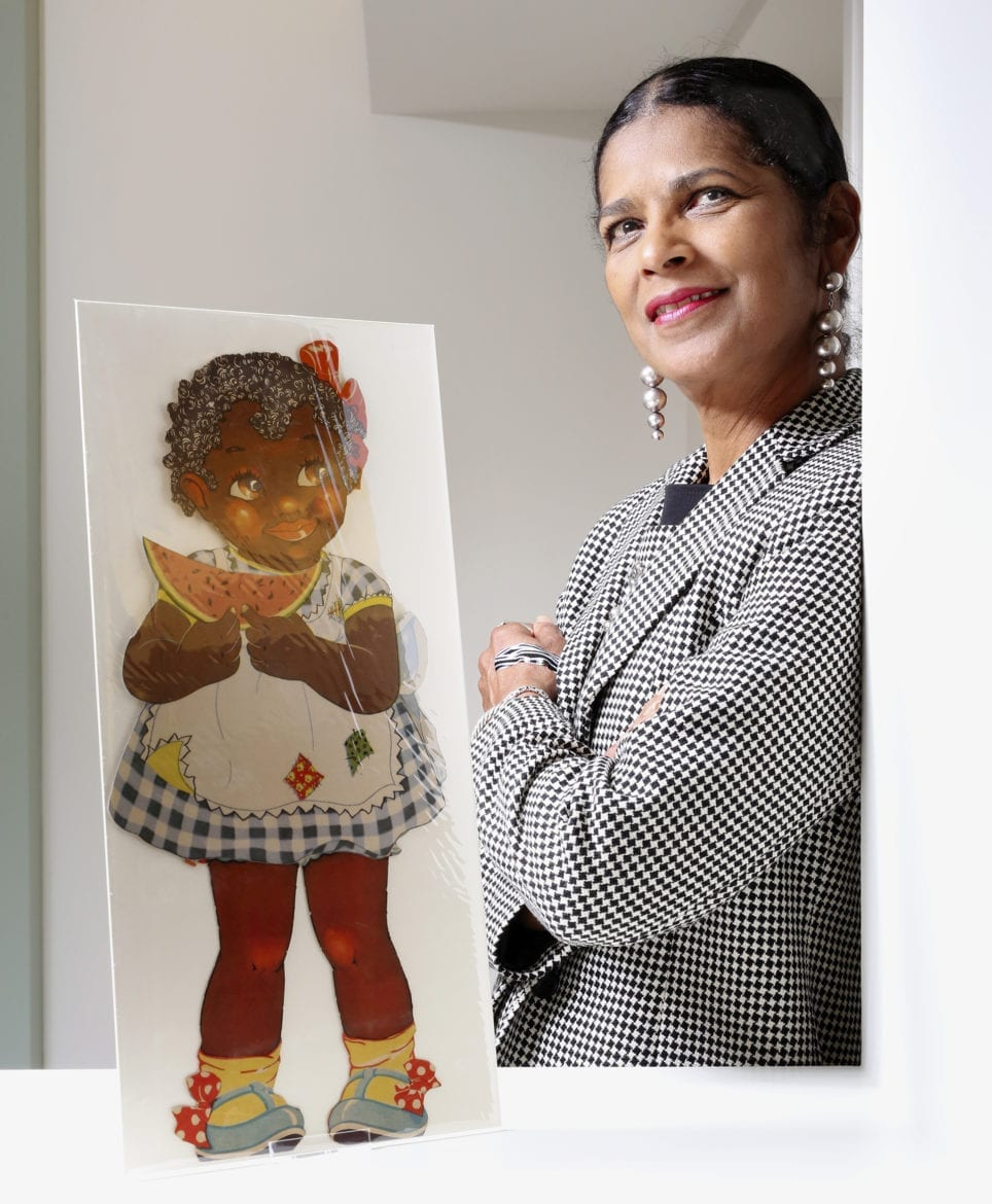 This photo shows Arabella Grayson standing next to her private collection of African American paper dolls.