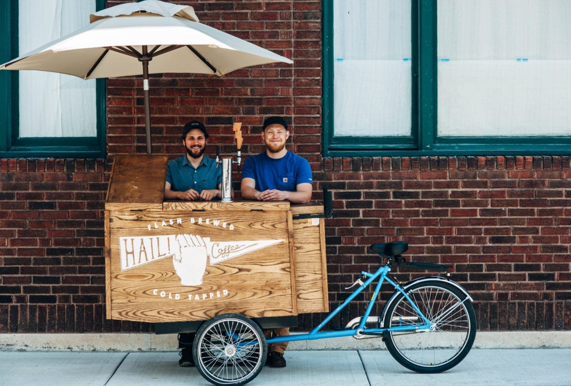 Two men stand behind their coffee cart.