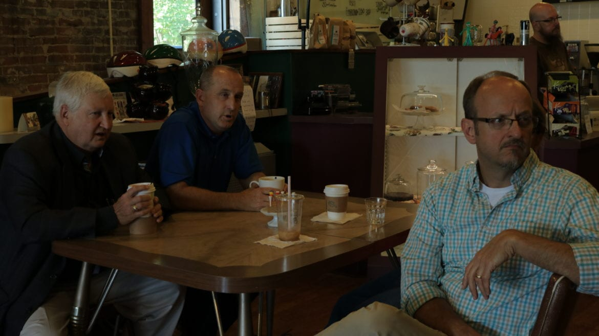 Three people seated over coffee at a table