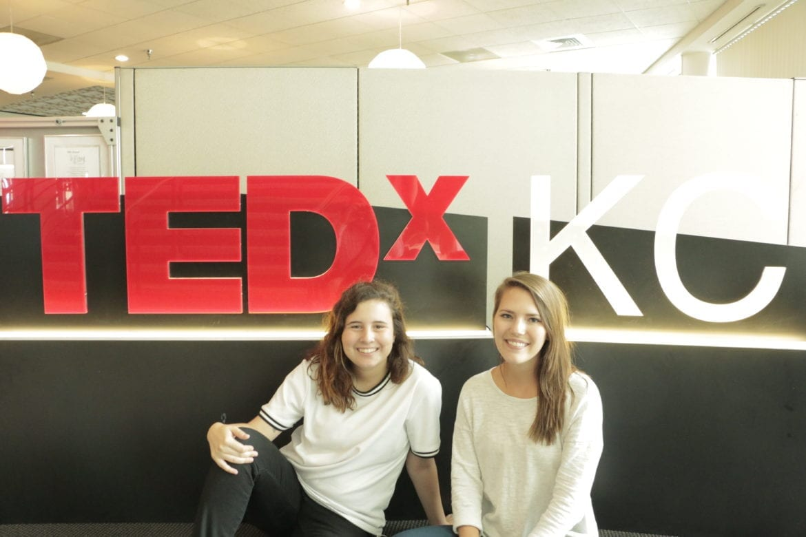 Two girls sit down in front of a TEDxKC sign indoors.