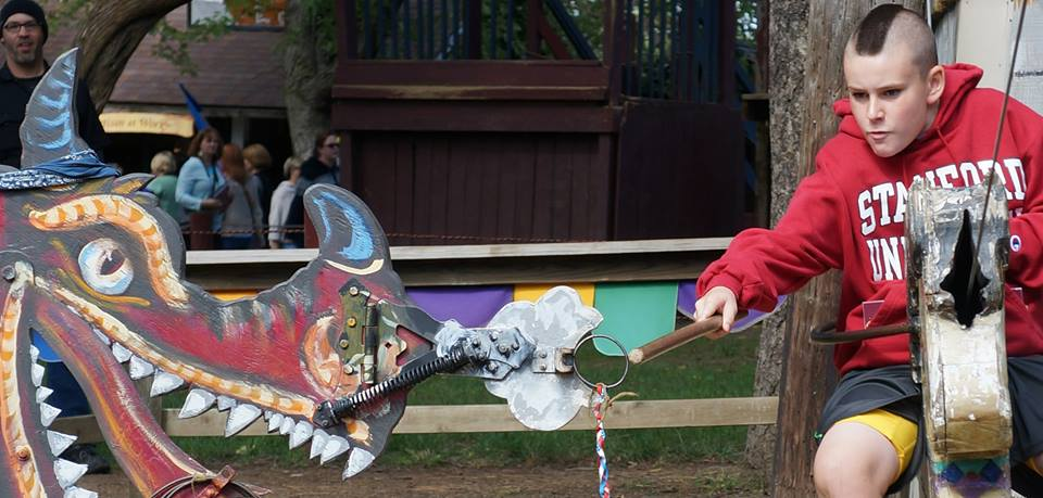 A festival-goer plays with a stationary dragon.