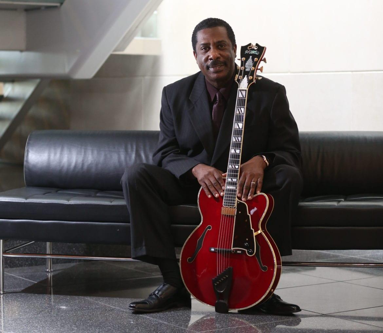 A man sitting holding a guitar.