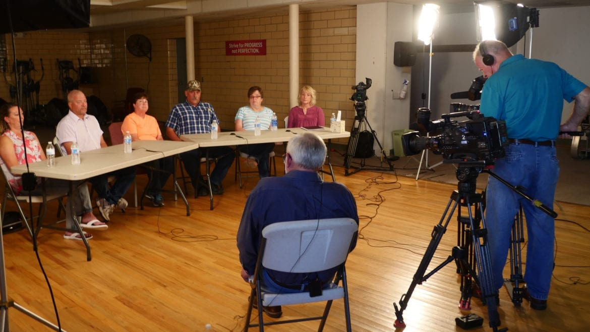 A reporter and videographers talking to seated family members