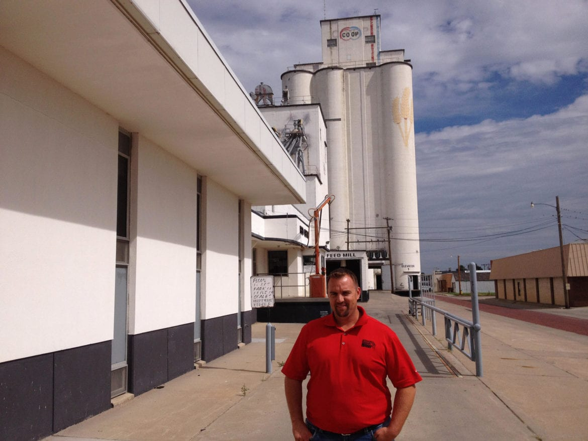 A man standing in front of a grain elevator.