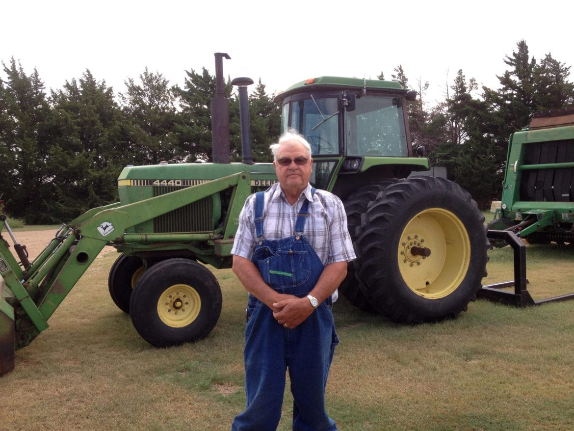 A man standing in front of his farm equipment.