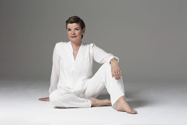 A woman sitting ad posing.