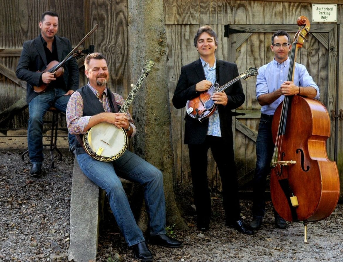 A bluegrass band posing with their instruments.