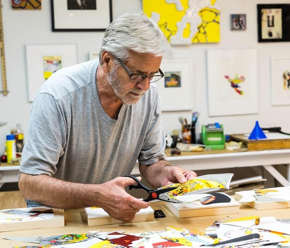 A man works on art at a desk.