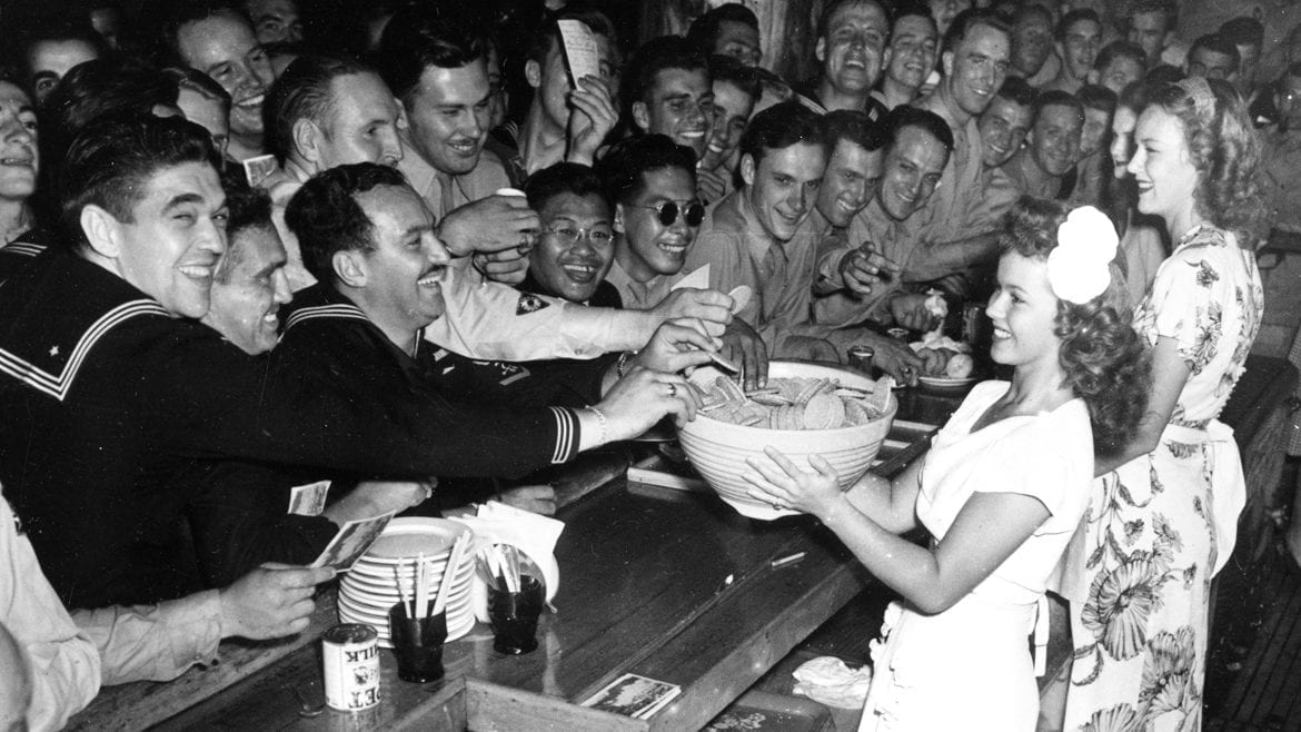 A young actress serves cookies to WWII Servicemen