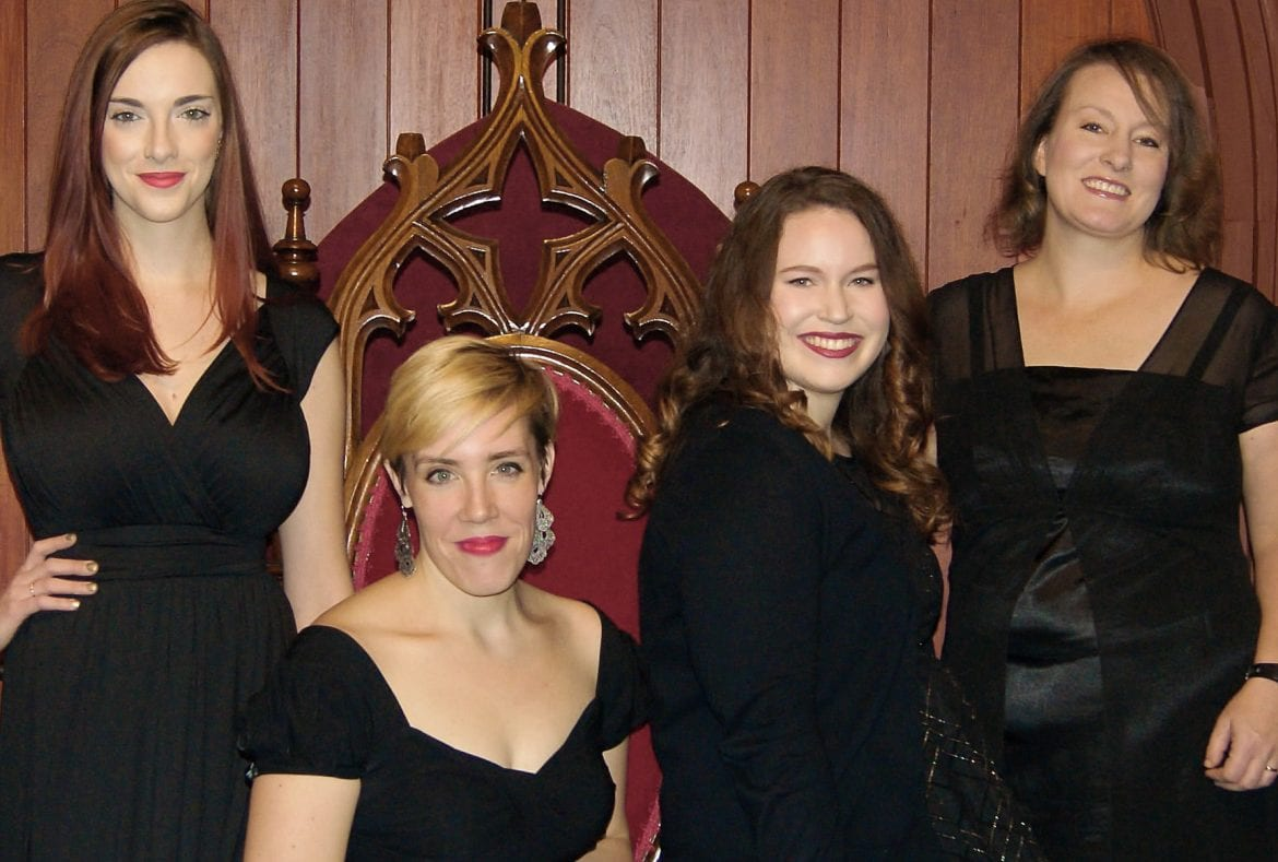 Four women sitting and standing in black dresses.
