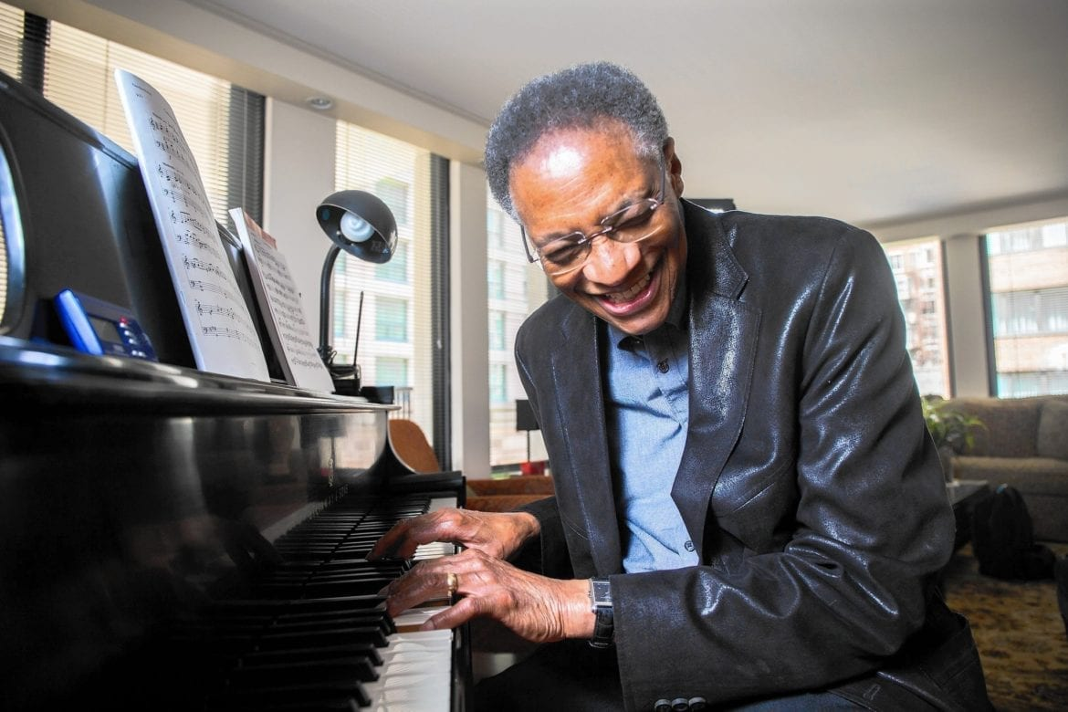 Ramsey Lewis plays the piano laughing.