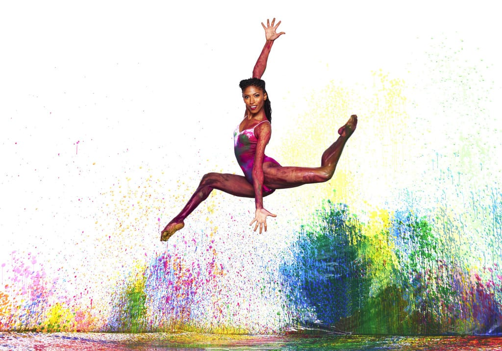 A woman jumping in the air with bright colors behind her.