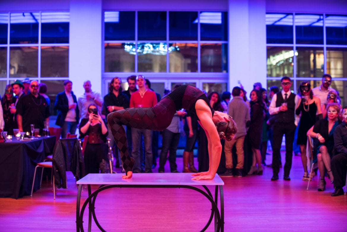 A woman doing a backbend on a able while at a party.