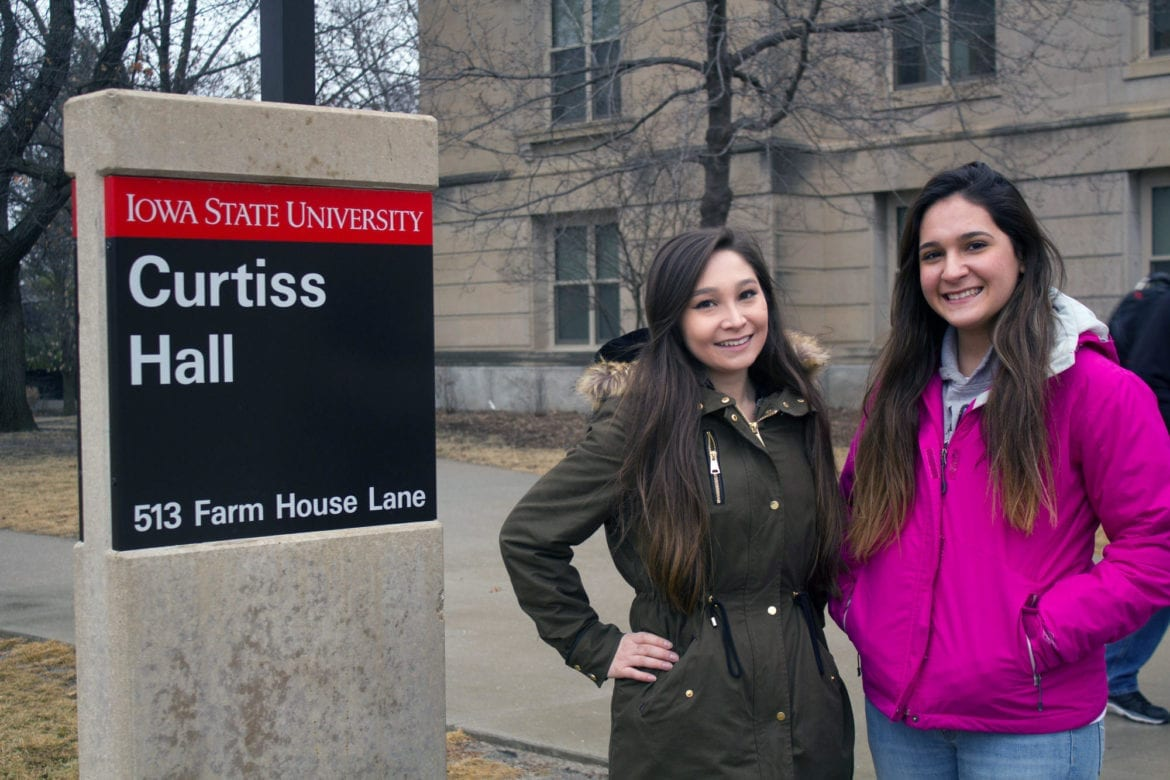 Two women standing on a college campus.