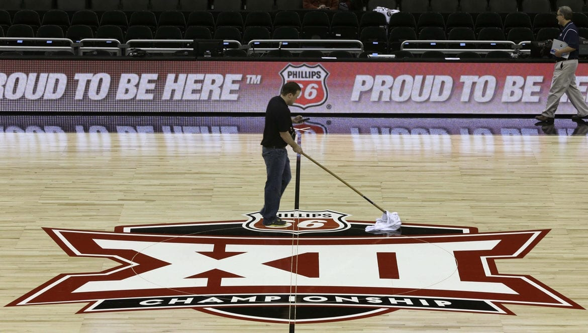A worker cleans a basketball court floor