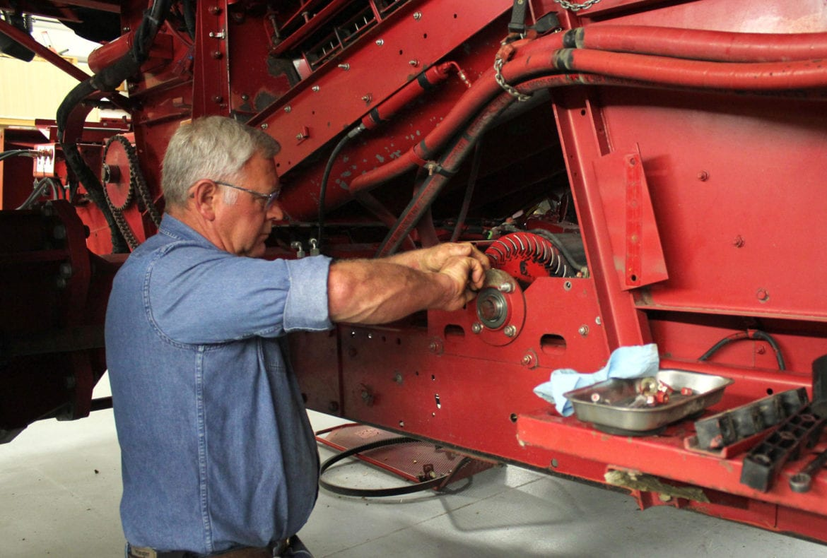 A man working on a tractor combine.