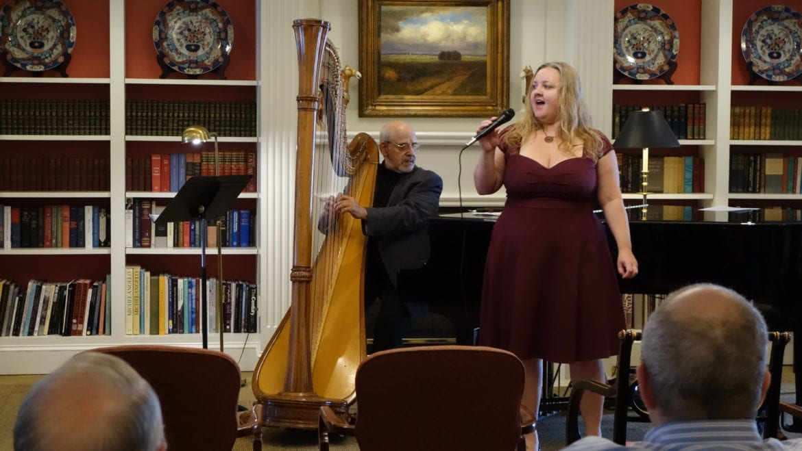 A woman singing next to a man playing a harp.