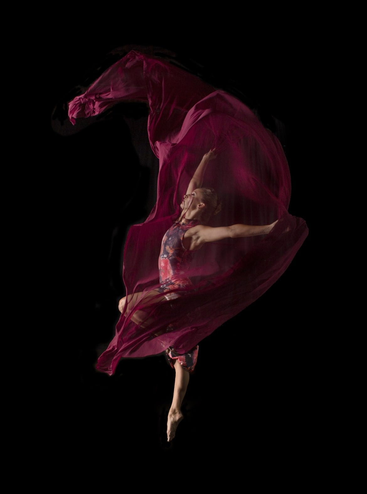 A woman draped in magenta, dancing.