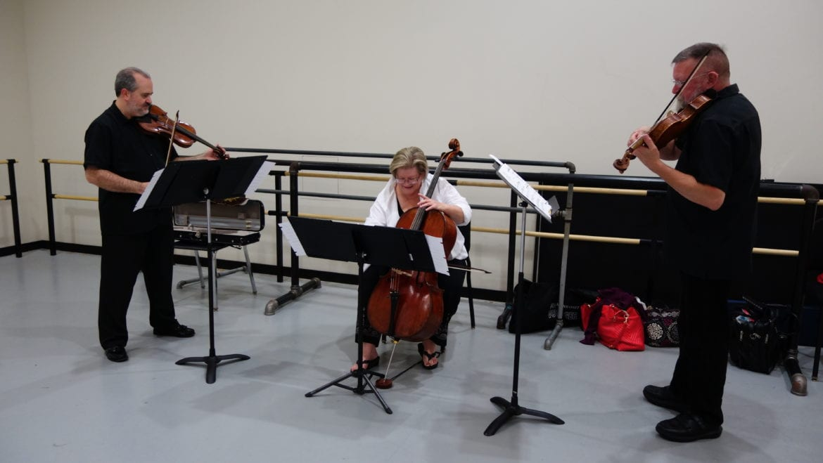 Three people playing string instruments.