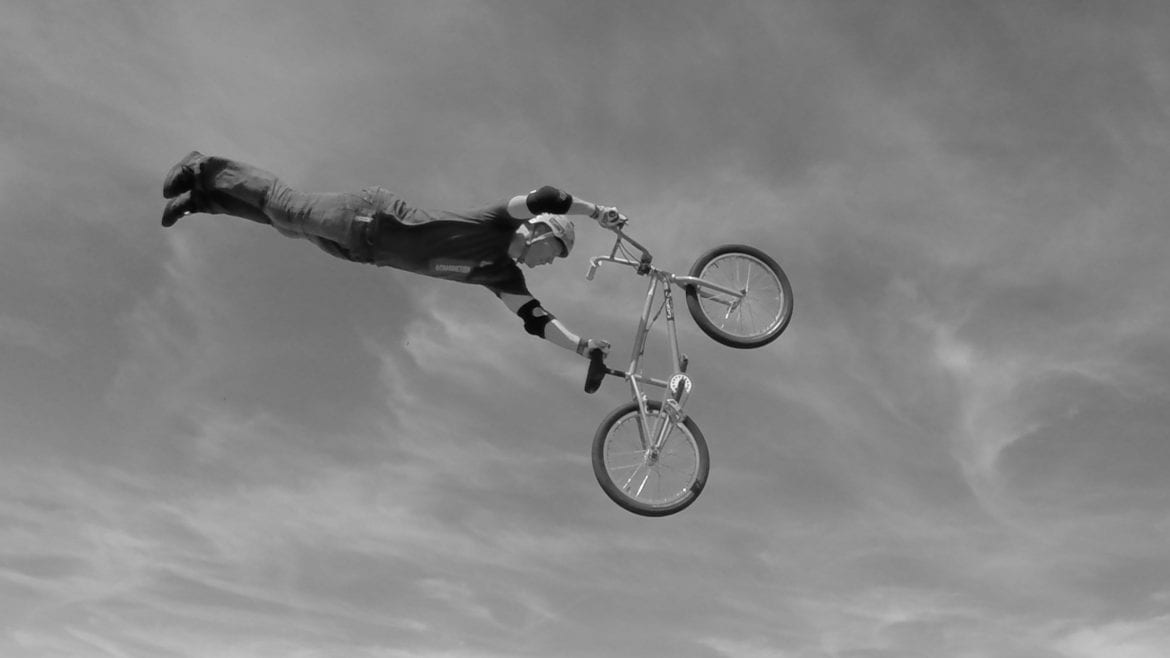 a man flies through the air doing stunts on a bike.