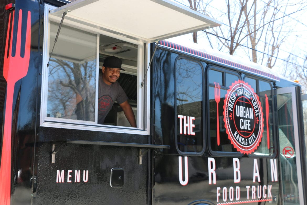 A man ready to serve food out of his food truck.