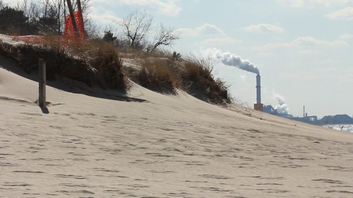 A beach with a visible smokestack in the background