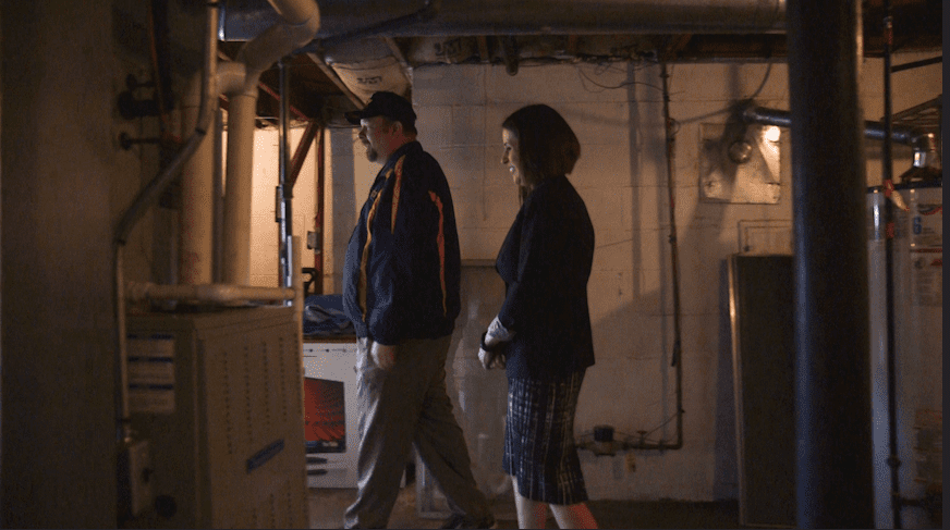 A man and woman walking in a basement