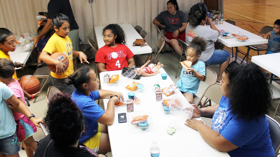 Kids gather in a gym to eat lunch from a government summer food program at Susquehanna Baptist Church, a food site in Independence, Missouri. (Lindsay Huth | Flatland)