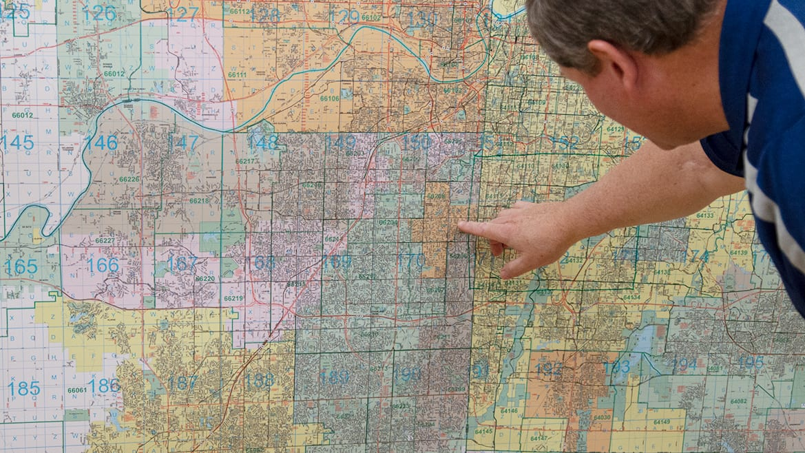 A man looks over a large wall map at Gallup maps in Kansas city
