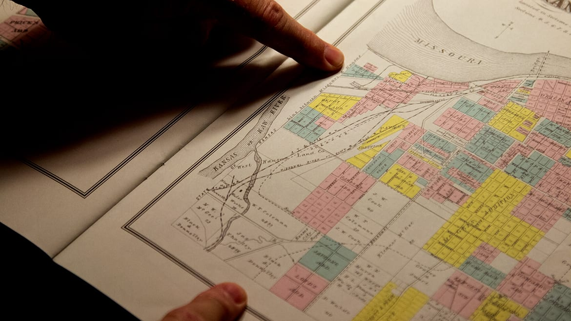 A man looks over an historical map in the Missouri Valley Special Collections