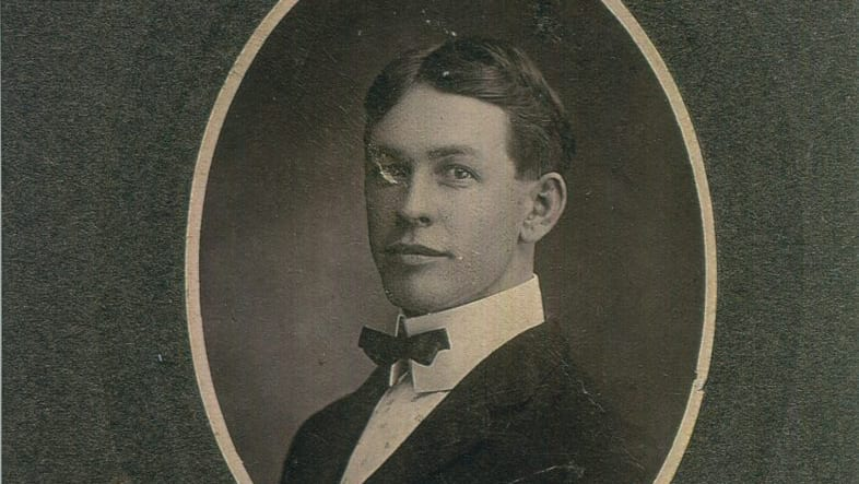 A black and white framed photo of a young man.