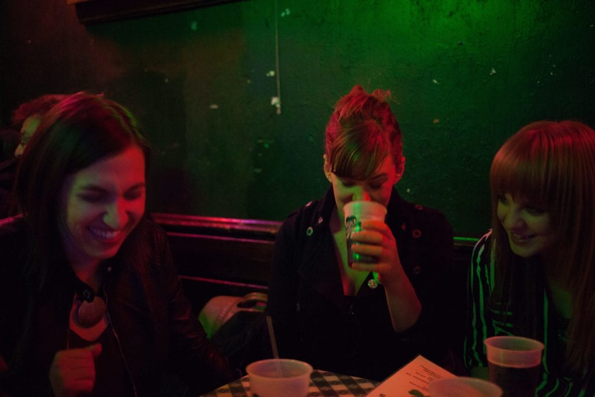 Three women in a dimly lit room siting at at table.