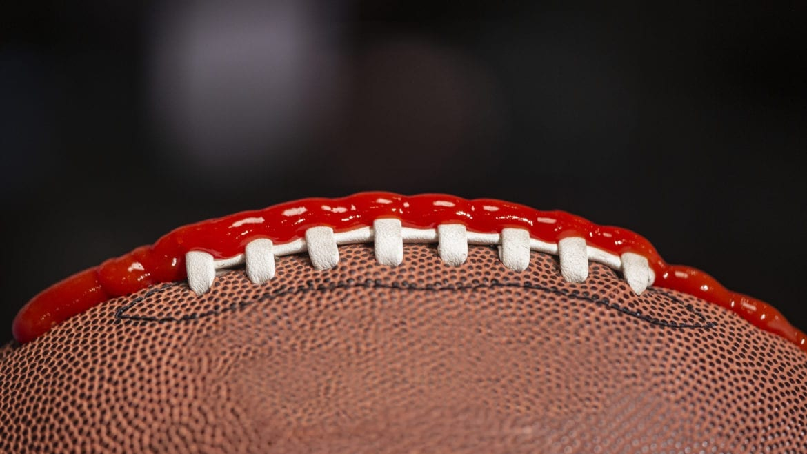 a football with ketchup on the laces